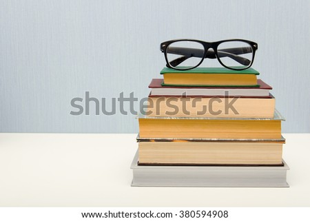 Pile of old books with the glasses on top
