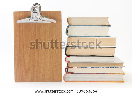 Pile of old books with wooden message board. - stock photo