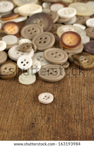 Pile of old fashioned buttons selective focus on white button in front - stock photo