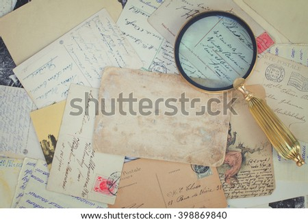 pile of old letters and antiques  vintage background with copy space, retro toned - stock photo