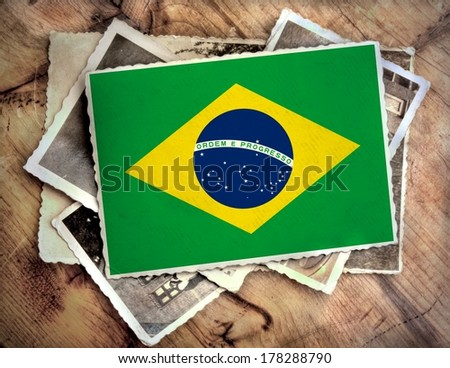pile of old photographs with on top a colorful image from the flag of Brazil - stock photo