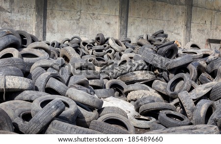 Pile of old used tires stocked for recycling - stock photo