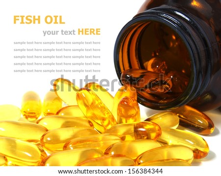 Pile of omega 3 fish oil capsules spilling out of a bottle - stock photo
