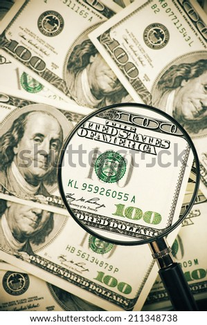Pile of one hundred dollar bills with magnifier. Top view. - stock photo
