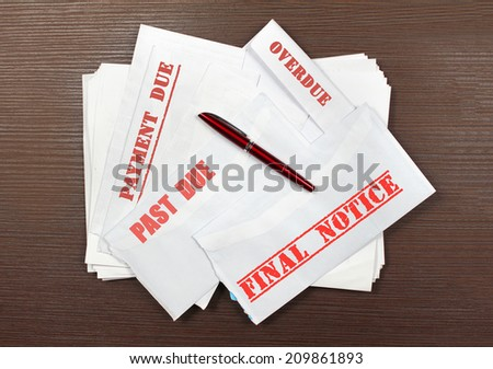 Pile of open envelopes with missed bill payment notices