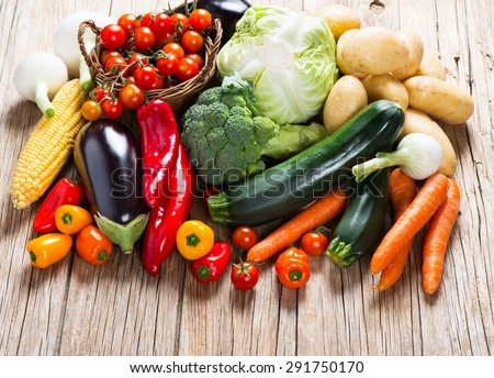 Pile of organic vegetables on a rustic wooden table - stock photo