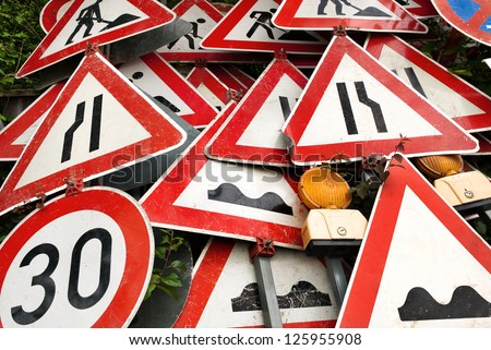 Pile of out-of-order red and white traffic signs - stock photo