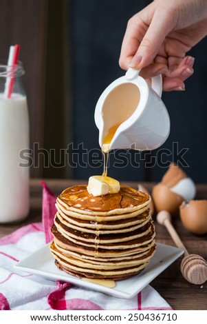 pile of Pancake with butter, pour honey, hand, American breakfast - stock photo