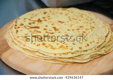 Pile of pancakes on a wooden board