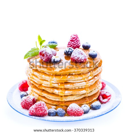 Pile of pancakes with blueberries and raspberries sprinkled with icing sugar and poured on with honey for breakfast on white background