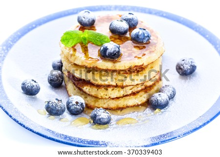 Pile of pancakes with blueberries sprinkled with icing sugar and poured on with honey for breakfast on white background