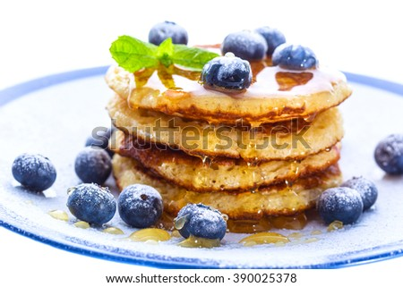 Pile of pancakes with blueberries sprinkled with icing sugar and poured on with honey for breakfast on white background - stock photo