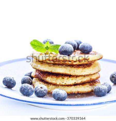 Pile of pancakes with blueberries sprinkled with icing sugar for breakfast on white background - stock photo