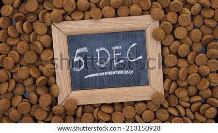 Pile of Pepernoten, typical Dutch treat for Sinterklaas on 5 december written on a chalkboard                      - stock photo