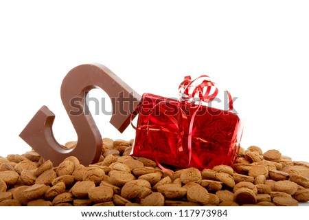 Pile of pepernoten with present and chocolate letter S over white background - stock photo