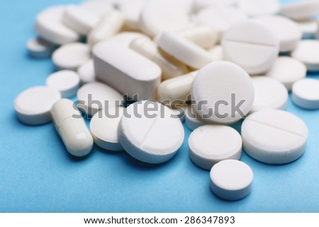 Pile of pills on color table, closeup