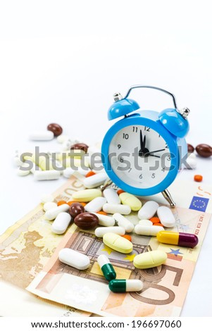 Pile of pills with banknotes and clock isolated with copy-space  - stock photo