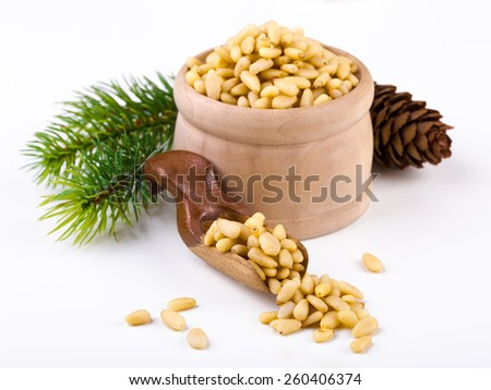 Pile of pine nuts with wooden scoop on white - stock photo