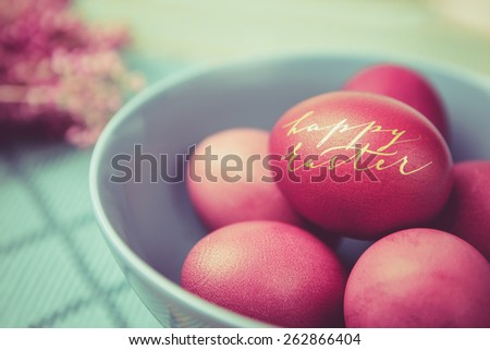 Pile of pink-red Easter eggs in a blue bowl with hand written with golden paint Eater greetings, vintage colors, shallow dof. - stock photo