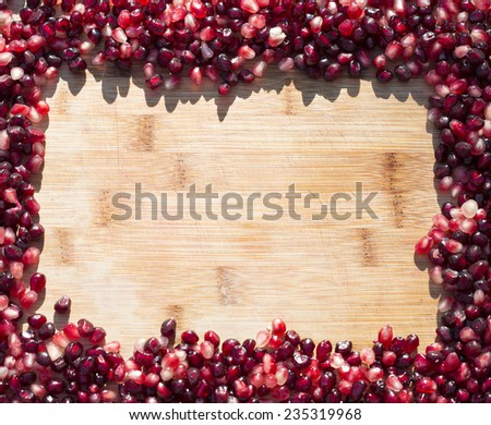 pile of pomegranate seeds forming rectangular border with a bamboo background - stock photo