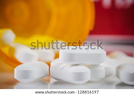pile of prescription pills with pill bottle in the background