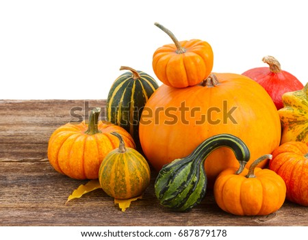 pile of raw orange pumpkins ripe on wooden table border isolated on white background