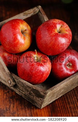 pile of red apples inside a wooden box - stock photo