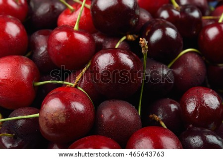 Pile of red cherries with drops of water on them, just removed from the refrigerator. Fresh fruit background texture.