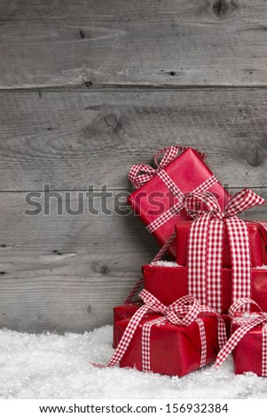 Pile of red Christmas gifts,snow on grey wooden background. - stock photo