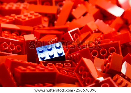 Pile of red color building blocks with selective focus and highlight on one particular blue block using available light. - stock photo