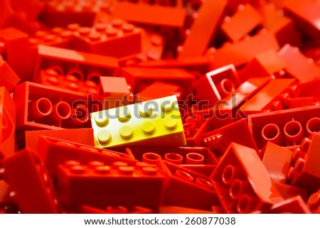 Pile of red color building blocks with selective focus and highlight on one particular yellow block using available light - stock photo