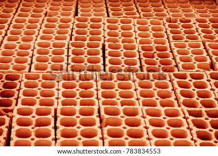 Pile Of Red Hollow Bricks With Large Holes Forming Lines In Repeating Geometric Pattern Similar To