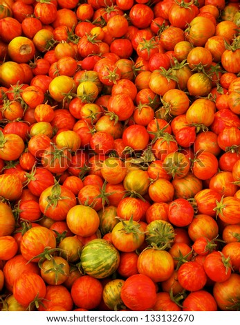 Pile of Red Juicy  Small Heirloom Tomatoes with softer background at the farmers market - stock photo