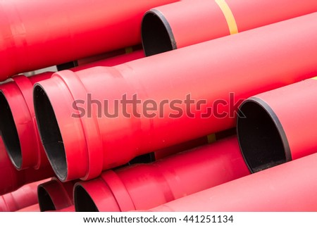 Pile of red pvc protective pipes - stock photo