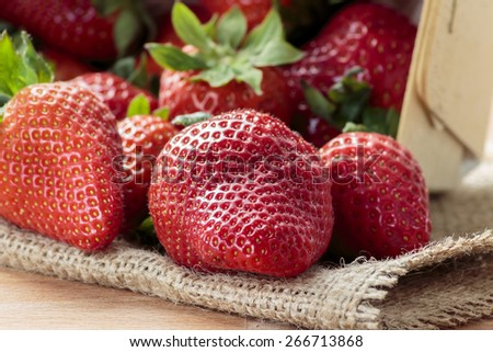 Pile of red strawberries on jute - stock photo