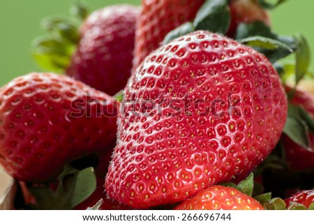 Pile of red strawberries with green background