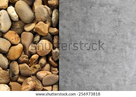 Pile of round pebble stones and cement floor - stock photo