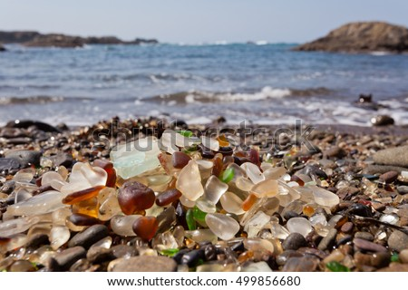 Pile of rounded glass shards or sea-glass of Fort Bragg, California, US with blurry Pacific Ocean background