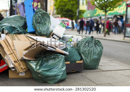 Pile of rubbish and litter on the sidewalk with busy pedestrians walking past - stock photo