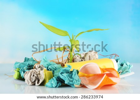 Pile of rubbish with plant on blue background - stock photo