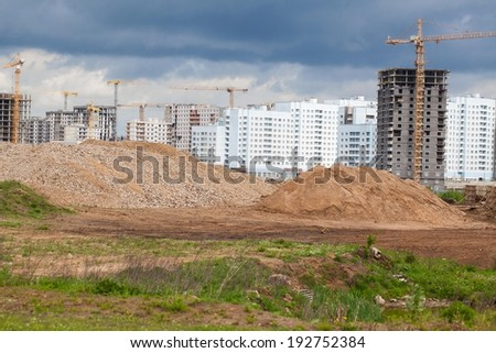 pile of sand on the complex construction. cranes on buildings