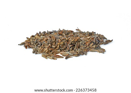 Pile of scattered caraway seeds on white background