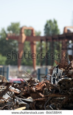 Pile of scrap iron and crane. Blurred background. Vertical image - stock photo