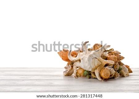Pile of seashells on  white wooden surface isolated on white. - stock photo