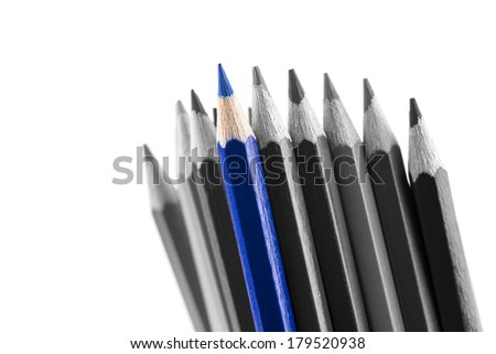 Pile of sharp colored pencils, with different hues, from black to light grey and a blue outstanding one, close-up on white background. - stock photo