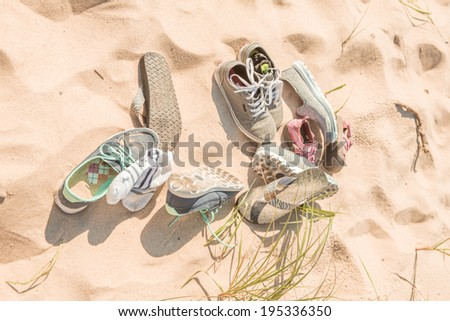 Pile of shoes on the beach - stock photo