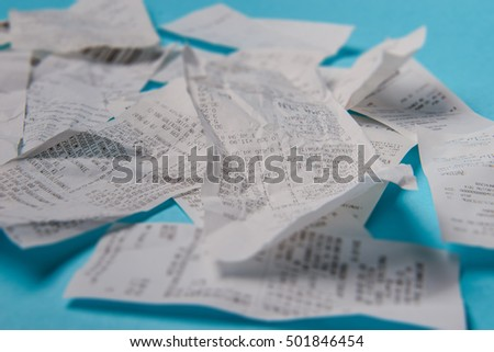 Pile of shopping receipts on a blue background
