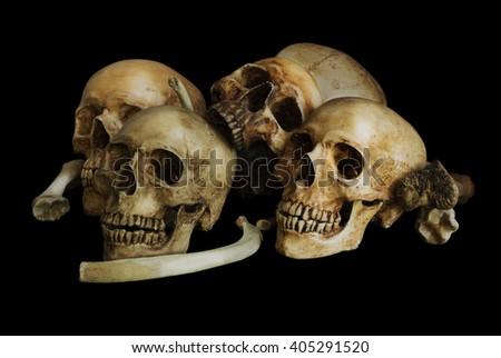 Pile of skulls and bones, isolated on black background  - stock photo