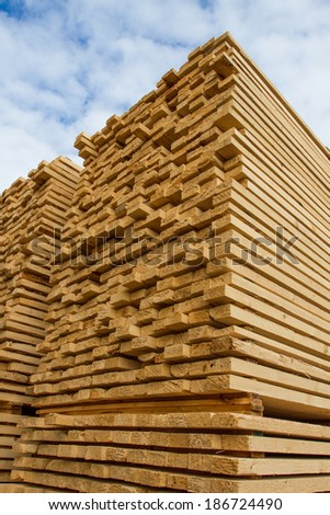 Pile of stacked rough cut lumber at a sawmill - stock photo