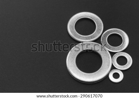Pile of stainless steel flat washers isolated on a dark background - stock photo